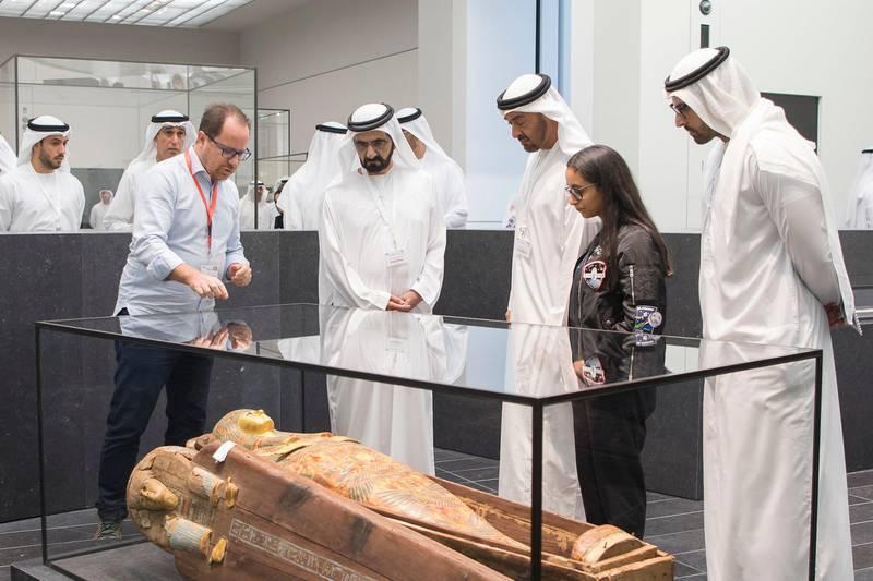 SAADIYAT ISLAND, ABU DHABI, UNITED ARAB EMIRATES -September 11, 2017: HH Sheikh Mohamed bin Zayed Al Nahyan Crown Prince of Abu Dhabi Deputy Supreme Commander of the UAE Armed Forces (4th R), HH Sheikh Mohamed bin Rashid Al Maktoum, Vice-President, Prime Minister of the UAE, Ruler of Dubai and Minister of Defence (3rd R), Alia Al Mansouri (2nd R) and HE Mohamed Khalifa Al Mubarak, Chairman of Abu Dhabi Tourism and Culture Authority (R) view the Funeral set of princess Henuttawy, during a tour of the Louvre Abu Dhabi.  ( Mohamed Al Raeesi for Crown Prince Court - Abu Dhabi ) ---