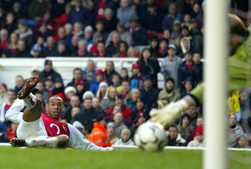 Arsenal's French forward Thierry Henry (L) puts the ball beyond  Wolverhampton keeper Michael Oakes (R) to score his second  goal during a premier league match at Highbury London, 26 December  2003. Arsenal defeated Wolverhampton 3-0.  AFP PHOTO / ODD ANDERSENNO TELCOS,WEBSITES SUBJECT TO DESCRIPTION OF LICENSE WITH FAPL AT:WWW.FAPLWEB.COM (Photo by ODD ANDERSEN / AFP)
