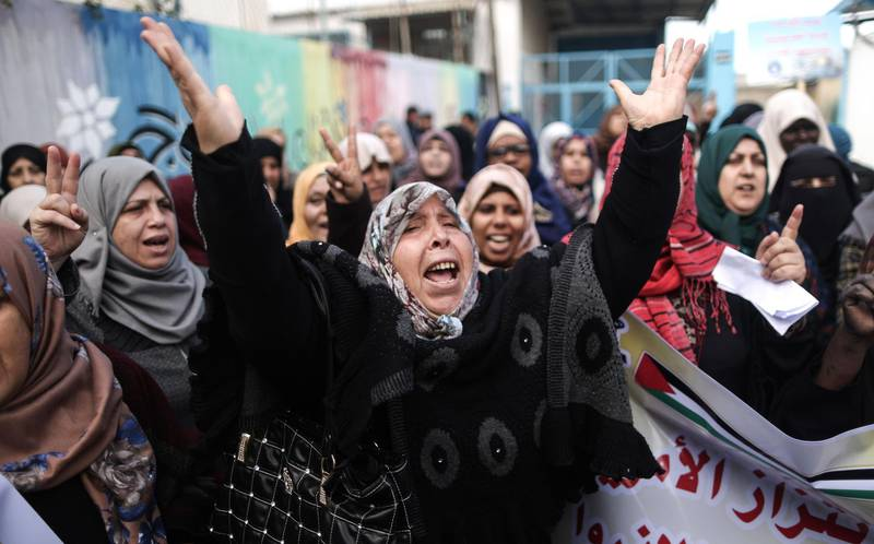 Palestinians protest outside of the United Nations' offices in al-Nusirat refugee camp in the Gaza strip on January 17, 2018 after the White House froze tens of millions of dollars in contributions. The agency provides Palestinian refugees and their descendants across the Middle East with services including schools and medical care, but Prime Minister Benjamin Netanyahu has long accused it of hostility toward Israel and called for its closure. / AFP PHOTO / MAHMUD HAMS