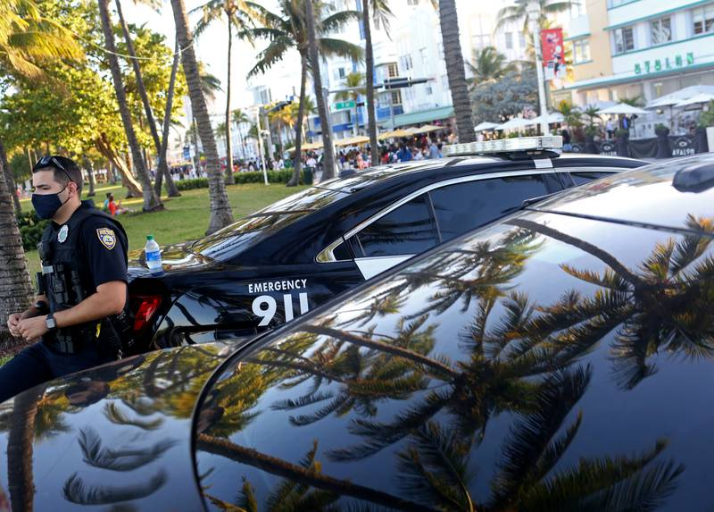 Miami Beach police stand by as people enjoy the bars and restaurants on South Beach during Spring Break in Miami, Florida, U.S., March 26, 2021.  REUTERS/Yana Paskova