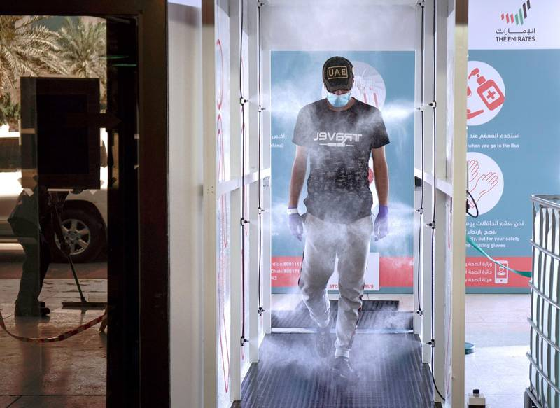 Abu Dhabi, United Arab Emirates, March 31, 2020.   A commuter enters the new sterilization area  and gets sprayed at the entrance of the Abu Dhabi Central Bus Terminal.Victor Besa / The NationalSection:  NAReporter: