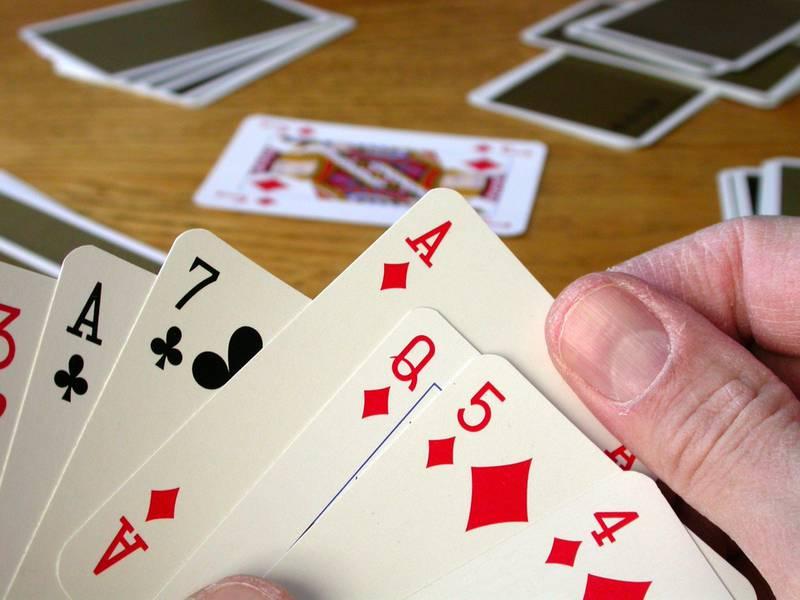 AC3J29 Man playing a card game