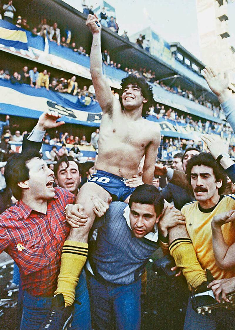 (FILE) This 1981 picture shoes Argentine soccer star Diego Armando Maradona, being carried by fans after winning the 1981 local Championship with Boca Juniors at La Bombonera stadium in Buenos Aires. Boca Juniors, the most popular football club in Argentina, celebrates on April 3rd, 2005, its centenary - from its creation by a group of football enthusiast in a humble neighbourhood of immigrants, until reaching the world's summit, and counting among its supporters with the most famous fan, Diego Armando Maradona.    AFP PHOTO/DIARIO POPULAR/NA       ARGENTINA OUT (Photo by DIARIO POPULAR / NA / AFP)
