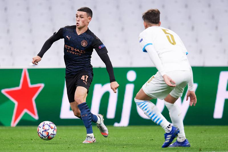 MARSEILLE, FRANCE - OCTOBER 27: Phil Foden of Manchester City FC runs with the ball past Leonardo Balerdi of Olympique de Marseille during the UEFA Champions League Group C stage match between Olympique de Marseille and Manchester City at Stade Velodrome on October 27, 2020 in Marseille, France. Football Stadiums around Europe remain empty due to the Coronavirus Pandemic as Government social distancing laws prohibit fans inside venues resulting in fixtures being played behind closed doors. (Photo by Alex Caparros/Getty Images)