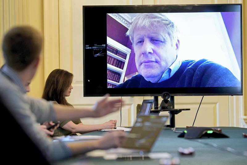 """A handout picture released by 10 Downing Street, the office of the British prime minister on March 28, 2020, shows an image of Britain's Prime Minister Boris Johnson on a screen as he remotely chairs the morning novel coronavirus Covid-19 meeting by video link, in Downing Street in central London. - The two men leading Britain's fight against the coronavirus -- Prime Minister Boris Johnson and his Health Secretary Matt Hancock -- both announced Friday they had tested positive for COVID-19, as infection rates accelerated and daily death rate rose sharply. (Photo by Andrew PARSONS / 10 Downing Street / AFP) / RESTRICTED TO EDITORIAL USE - MANDATORY CREDIT """"AFP PHOTO / 10 DOWNING STREET / ANDREW PARSONS / HANDOUT"""" - NO MARKETING - NO ADVERTISING CAMPAIGNS - DISTRIBUTED AS A SERVICE TO CLIENTS"""