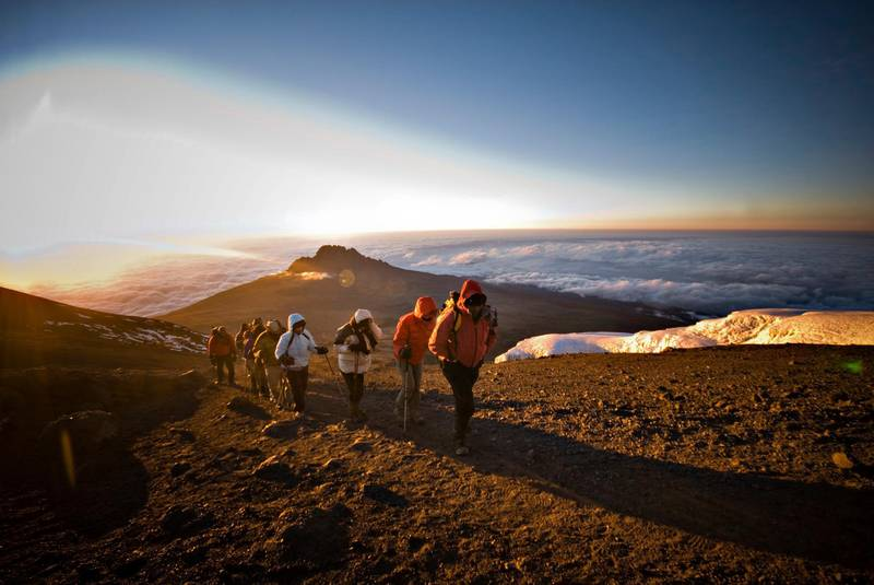 A team of hikers approach the summit of Mt. Kilimanjaro at sunrise. Getty Images