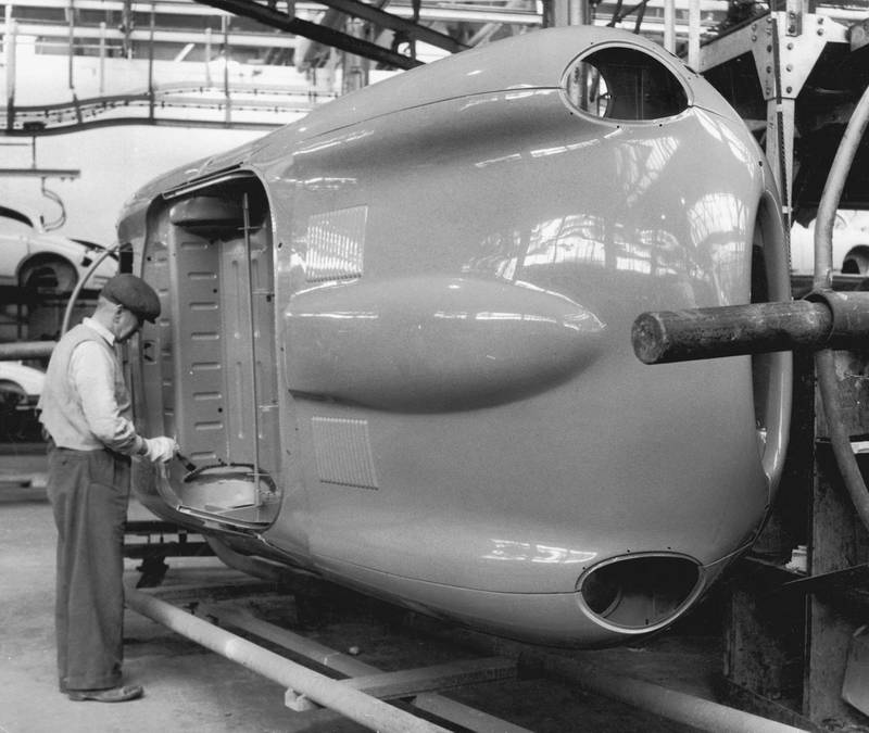 A worker touches up the paintwork on an E-Type Jaguar body shell at the company's Coventry works, 25th May 1961. (Photo by Chris Ware/Keystone Features/Hulton Archive/Getty Images)