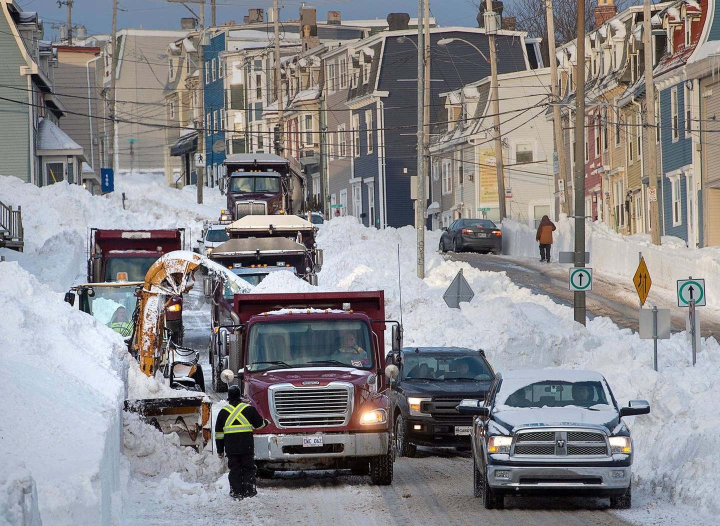 Workers continue to remove snow from the streets in St. John's, Newfoundland and Labrador, on Tuesday, Jan. 21, 2020. The state of emergency ordered by the City of St. John's continues for a fifth day, leaving most businesses closed and most vehicles off the roads in the aftermath of the major winter storm that hit the Newfoundland and Labrador capital. The city has allowed grocery and convenience stores to open for limited hours to let residents restock their food supply. (Andrew Vaughan/The Canadian Press via AP)