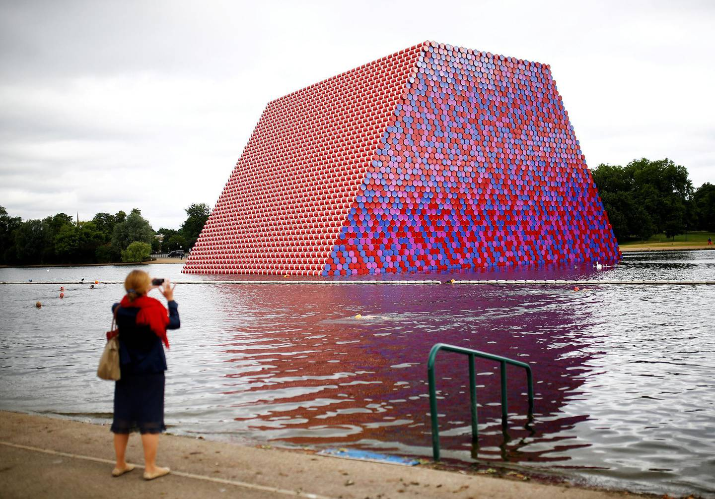"""FILE PHOTO: A woman photographs swimmers exercising in the Serpentine River in front of Christo's """"The London Mastaba"""", in Hyde Park, London, Britain, June 19, 2018. REUTERS/Henry Nicholls/File Photo"""