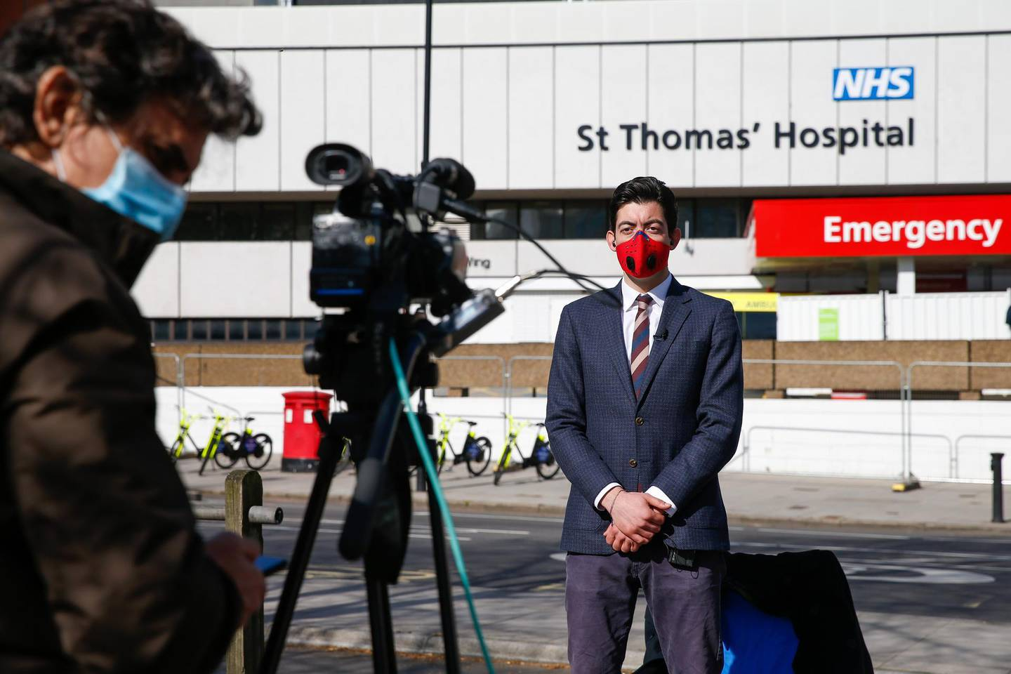 Members of the media wearing protective face masks broadcast from outside St Thomas' Hospital, operated by Guy's and St Thomas' NHS Foundation Trust, where U.K. Prime Minister Boris Johnson is being cared for in intensive care after struggling to shake off covid-19, in London, U.K., on Tuesday, April 7, 2020. The U.K. is facing a leadership crisis as it heads into the peak of the coronavirus pandemic, withJohnsonin intensive care and his government under pressure to get a grip on the outbreak. Photographer: Hollie Adams/Bloomberg