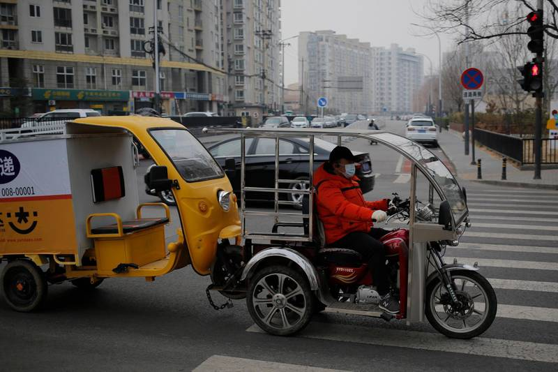 epa08274148 A man wearing a mask pulls a tricycle with his tricycle in Beijing, China, 06 March 2020. The coronavirus outbreak has claimed over 3,000 lives worldwide.  EPA/WU HONG