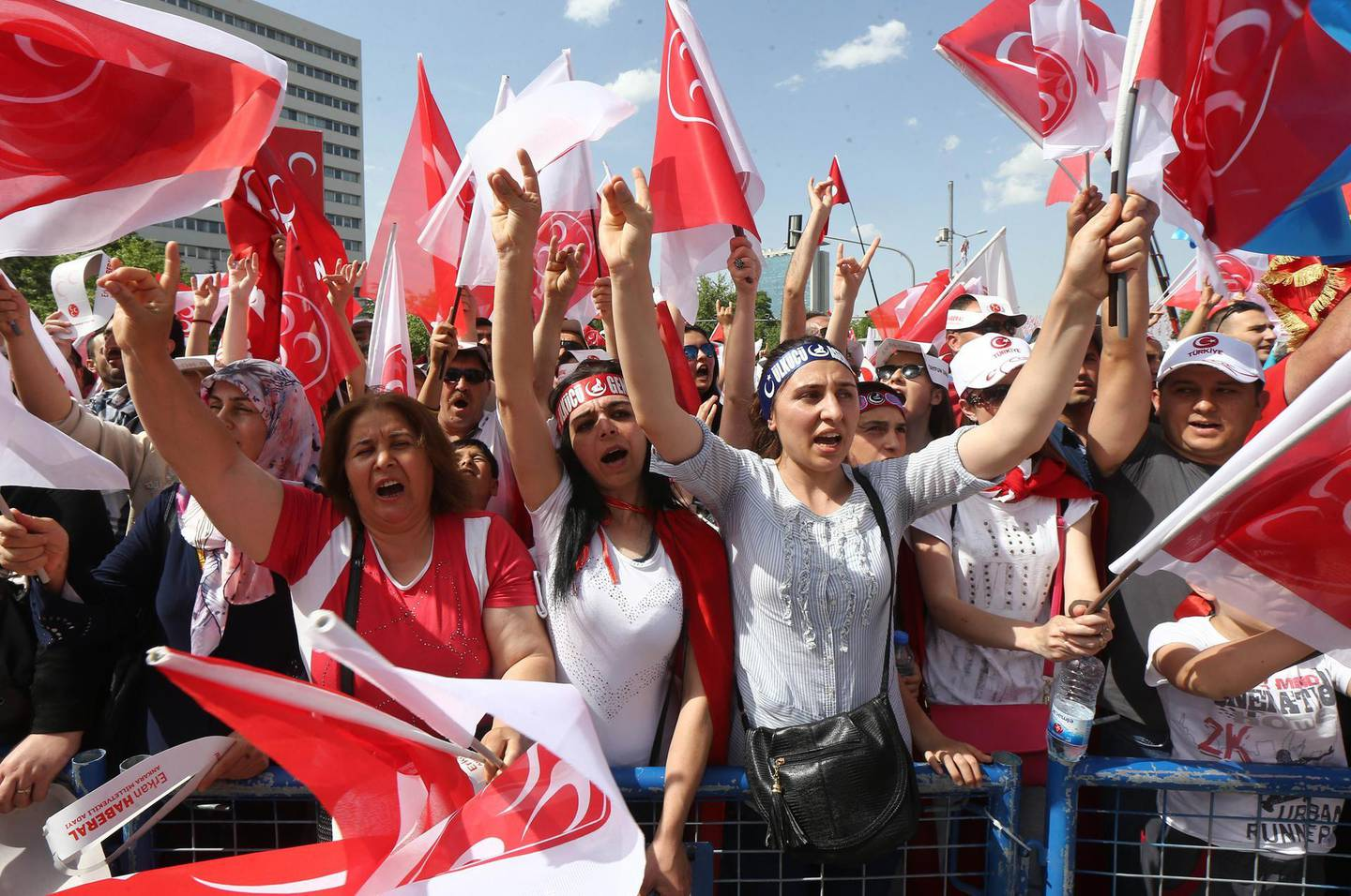 """People gestures the """"Grey Wolves"""" salutation and wave flafs during an election rally of Turkey's opposition Nationalist Action Party (MHP) May 24, 2015 in Ankara, ahead of the June 7 general elections. AFP PHOTO/ADEM ALTAN (Photo by ADEM ALTAN / AFP)"""