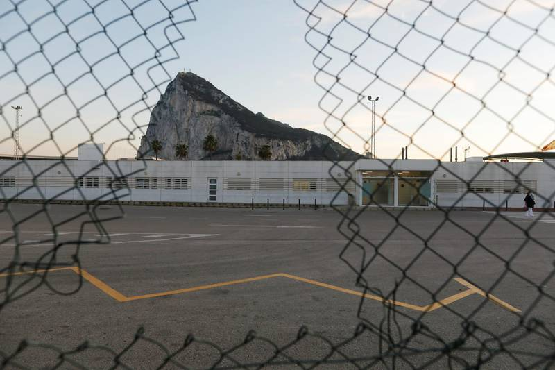 A person crosses the Spanish border from Gibraltar side in front of the Rock of the British overseas territory of Gibraltar, historically claimed by Spain, after Britain and the European Union agreed terms of a trade deal on Brexit on Thursday, in La Linea de la Concepcion, southern Spain, December 24, 2020. REUTERS/Jon Nazca