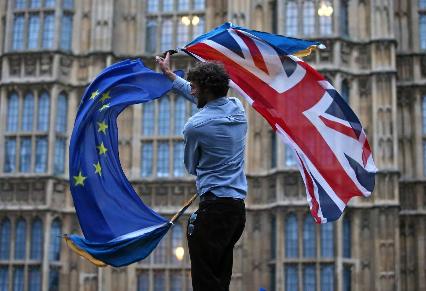 (FILES) In this file photo taken on June 28, 2016 a man waves both a Union flag and a European flag together on College Green outside The Houses of Parliament at an anti-Brexit protest in central London. Britain said on Thursday, December 24, 2020 an agreement had been secured on the country's future relationship with the European Union, after last-gasp talks just days before a cliff-edge deadline. / AFP / JUSTIN TALLIS