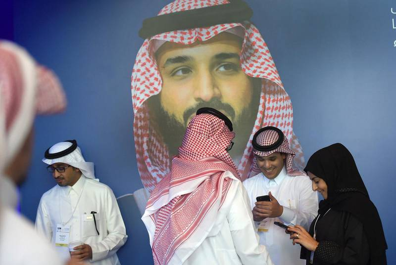 """Saudis chat and check their phones in front of a poster of Saudi Crown Prince Mohammed bin Salman during the """"MiSK Global Forum"""" held under the slogan """"Meeting the Challenge of Change"""" in Riyadh, on November 15, 2017.  The MiSK Global Forum brings together global CEOs international policymakers and heads of tech giants. / AFP PHOTO / FAYEZ NURELDINE"""