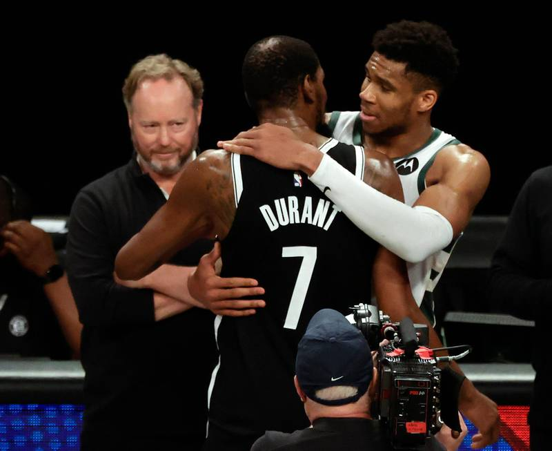 epa09287475 Milwaukee Bucks forward Giannis Antetokounmpo (R) of Greece hugs Brooklyn Nets forward Kevin Durant (C) in front of Milwaukee Bucks head coach Mike Budenholzer (L) after the Milwaukee Bucks defeated the Brooklyn Nets in overtime during game seven of the 2021 NBA Eastern Conference Semi-Finals basketball playoff series between the Milwaukee Bucks and the Brooklyn Nets at the Barclays Center in Brooklyn, New York, USA, 19 June 2021.  EPA/JASON SZENES SHUTTERSTOCK OUT