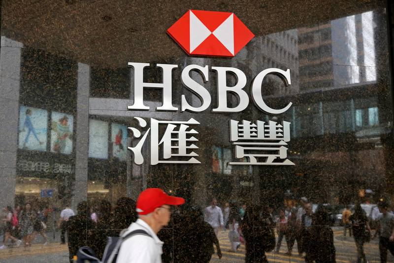 People walk past a branch of HSBC bank in Hong Kong, Friday, May 4, 2018. Global bank HSBC says pretax profits dipped in the latest quarter because of higher operating costs. The bank also said Friday that it's planning to buy back up to $2 billion in shares. It was its first quarterly earnings report under new Chief Executive John Flint, who took over in February.(AP Photo/Kin Cheung)
