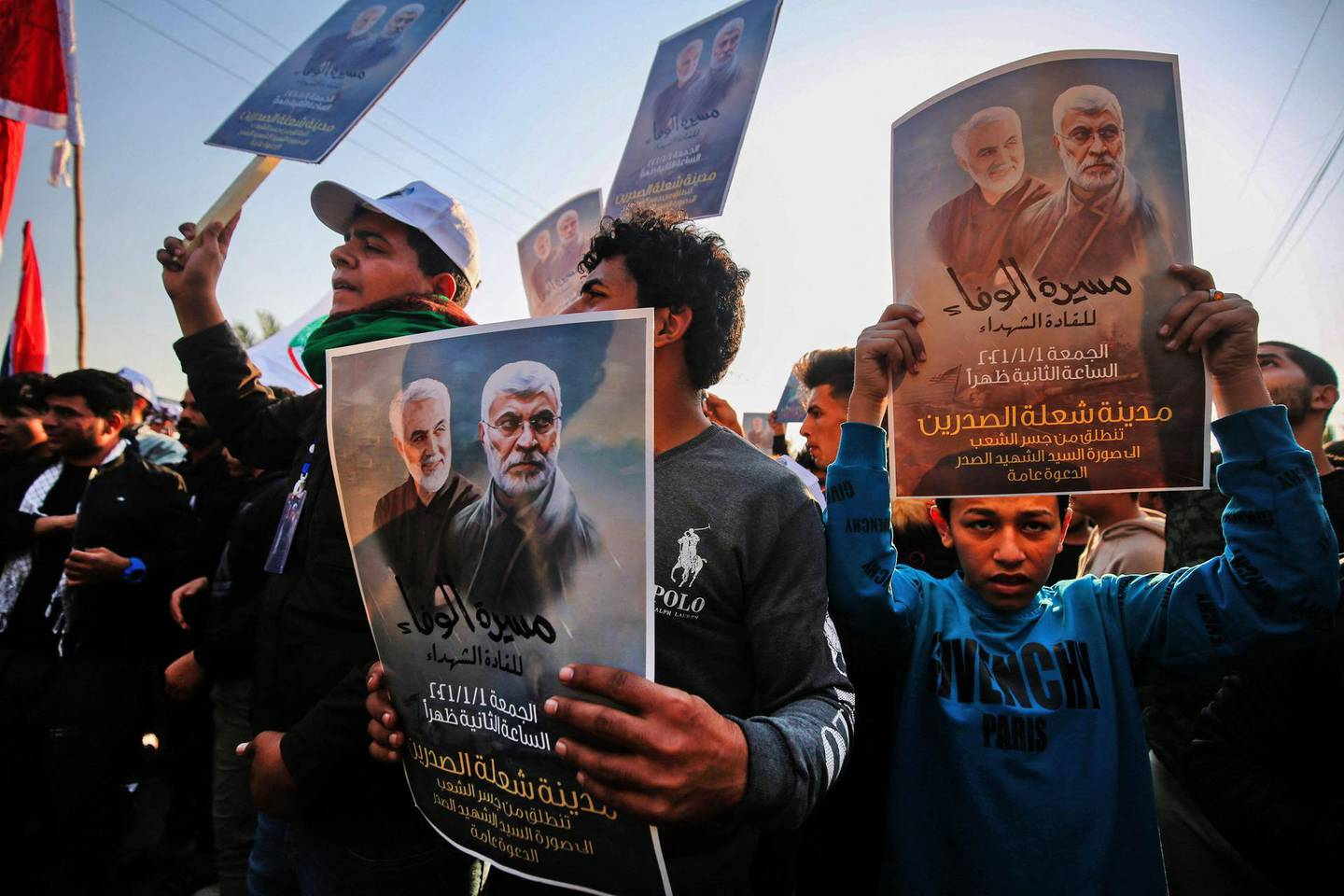 """(FILES) In this file photo taken on January 01, 2021 Iraqi supporters of the Hashed al-Shaabi paramilitary carry portraits of  Iraqi commander Abu Mahdi al-Muhandis and Iranian Revolutionary Guards commander Qasem Soleimani during a demonstration in Baghdad's western Shoala neighbourhood, demanding the expulsion of US forces from Iraq  At least 17 pro-Iran fighters were killed in US strikes in Syria at the Iraq border overnight, the Syrian Observatory for Human Rights said on February 26, 2021. """"The strikes destroyed three lorries carrying munitions... There were many casualties. Preliminary indications are that at least 17 fighters were killed, all members of Popular Mobilisation Forces,"""" the director of the SOHR, Rami Abdul Rahman, told AFP, referencing the powerful coalition of pro-Iran Iraqi paramilitaries.  / AFP / AHMAD AL-RUBAYE"""