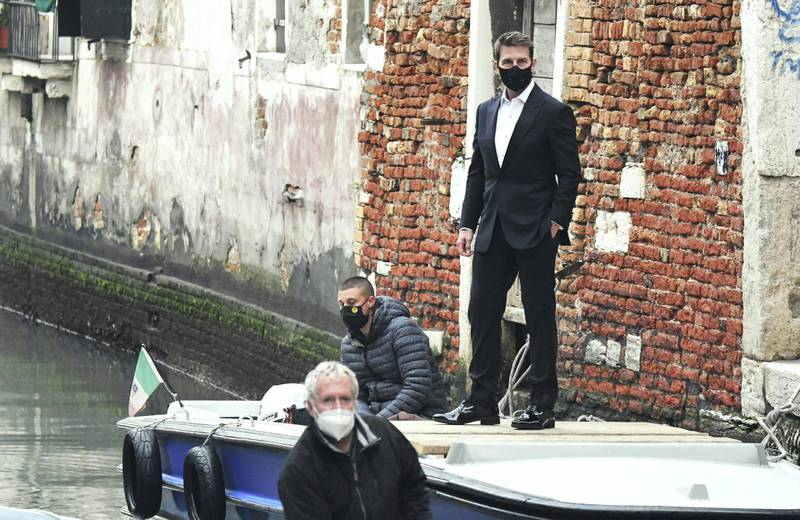 """US actor Tom Cruise stands on a boat during the shooting of the movie """"Mission Impossible: Lybra"""" in Venice on October 20, 2020. (Photo by ANDREA PATTARO / AFP)"""