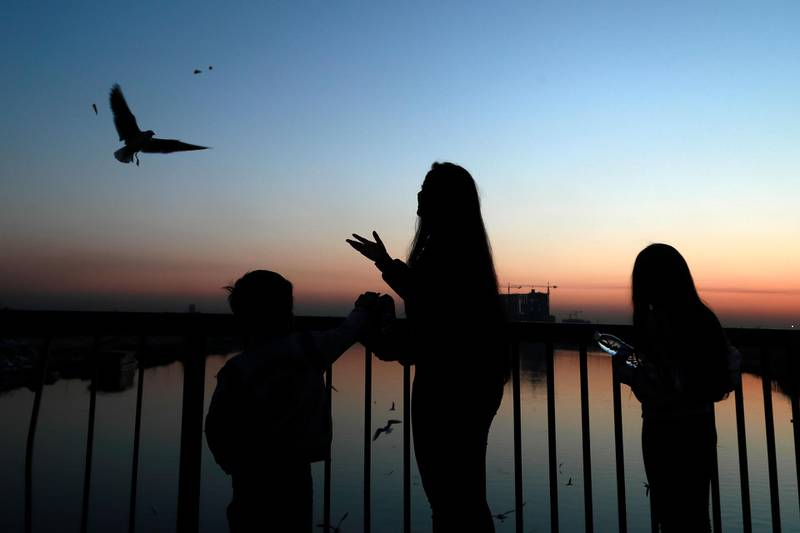 People feed seagulls on the a bridge over the Tigris river as the sun sets in Baghdad, Iraq, Monday, Jan. 11, 2021. (AP Photo/Hadi Mizban)