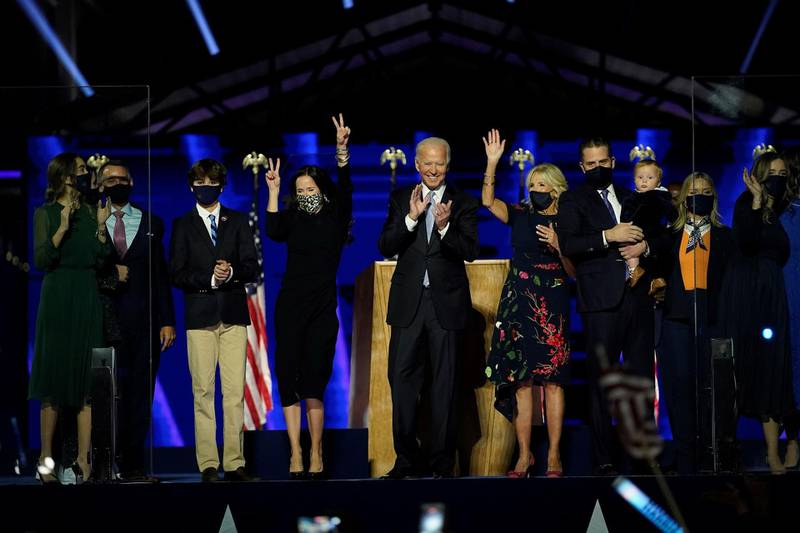 TOPSHOT - US President-elect Joe Biden, cente, with his wife Jill Biden and members of this family  salute the crowd on stage after delivering remarks in Wilmington, Delaware, on November 7, 2020. / AFP / POOL / Andrew Harnik