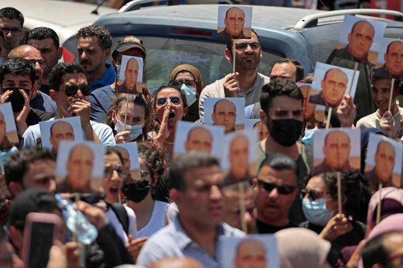 """Protesters take part in a demonstration calling for Palestinian president Mahmud Abbas to quit in Ramallah in the occupied West Bank on June 24, 2021, following the death of Palestinian human rights activist Nizar Banat who died shortly after being arrested by Palestinian Authority (PA) security forces.  The family of Nizar Banat claimed he was beaten to death, sparking condemnation from human rights activists, marches in the West Bank city of Ramallah, and calls for an inquiry, including from the European Union, who said they were """"shocked and saddened"""". Banat, 43, from the flashpoint city of Hebron, was arrested in a dawn raid by Palestinian Authority (PA) security forces, Hebron governor Jibrin al-Bakri said.  / AFP / ABBAS MOMANI"""