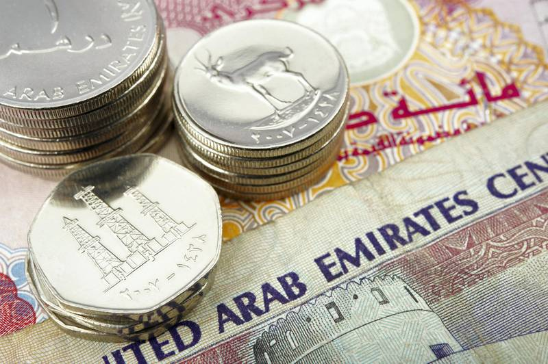 united arab emirates dirham banknote and coins. the coin depict arabian oryx and oil derricks.