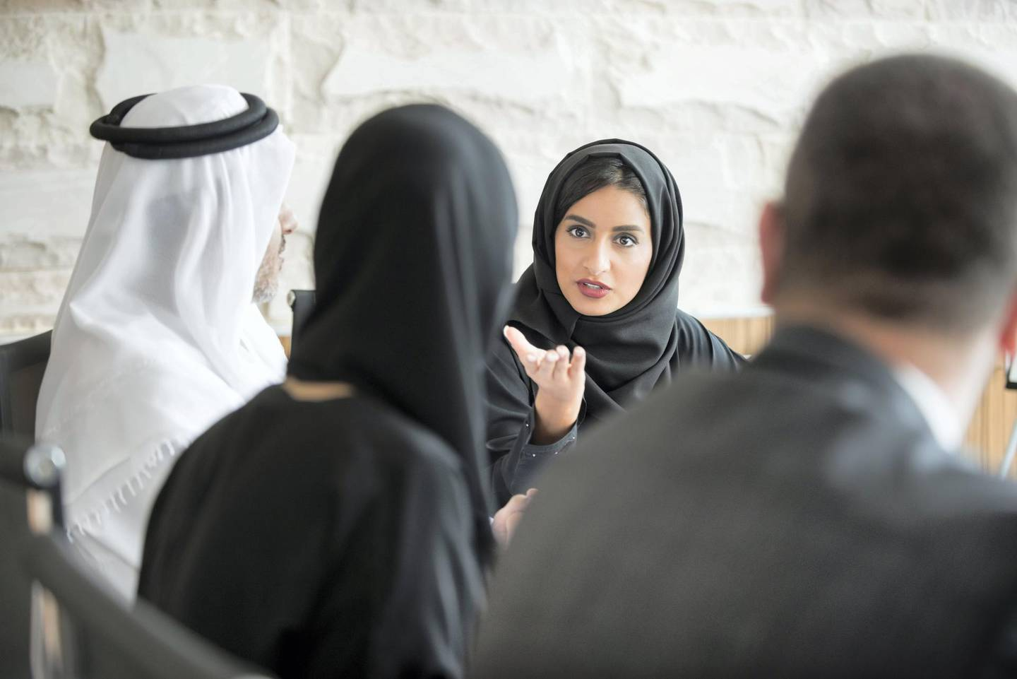 A photo of young and confident Arab businesswoman discussing in a meeting. Emirati woman wearing traditional abaya. Middle Eastern professional female is gesturing towards colleague while sitting in board room meeting.