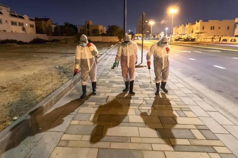 SHARJAH, UNITED ARAB EMIRATES. 26 MARCH 2020. Sharjah Municipal staff spray and disinfect the sidewalk along the Al Muntazah Str area of Sharjah near the Ajman border. . (Photo: Antonie Robertson/The National) Journalist: None. Section: National.