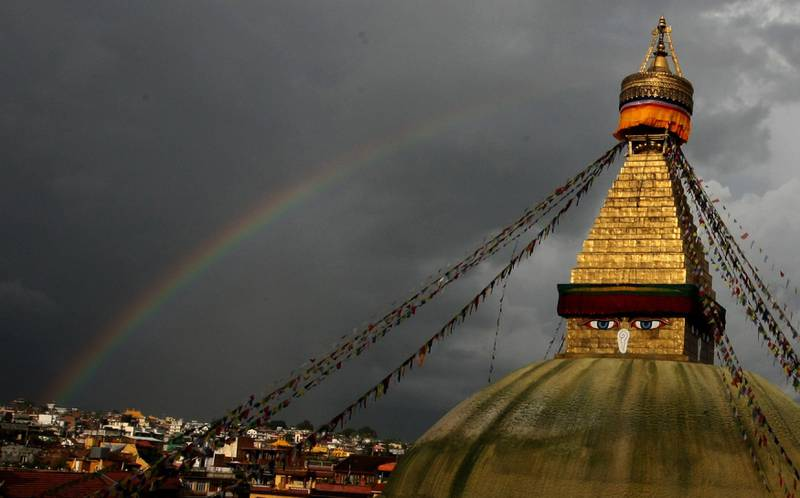 Buddhist pilgrims and tourists visit the Boudhanath Stupa, as a rainbow stretches over the horizon, in Kathmandu on September 9, 2010. Boudhanath Stupa, which was declared a world heritage site by UNESCO in 1979, is situated on the eastern side of Kathmandu and is  one of the largest in the world. AFP PHOTO/Prakash MATHEMA  *** Local Caption ***  144340-01-08.jpg