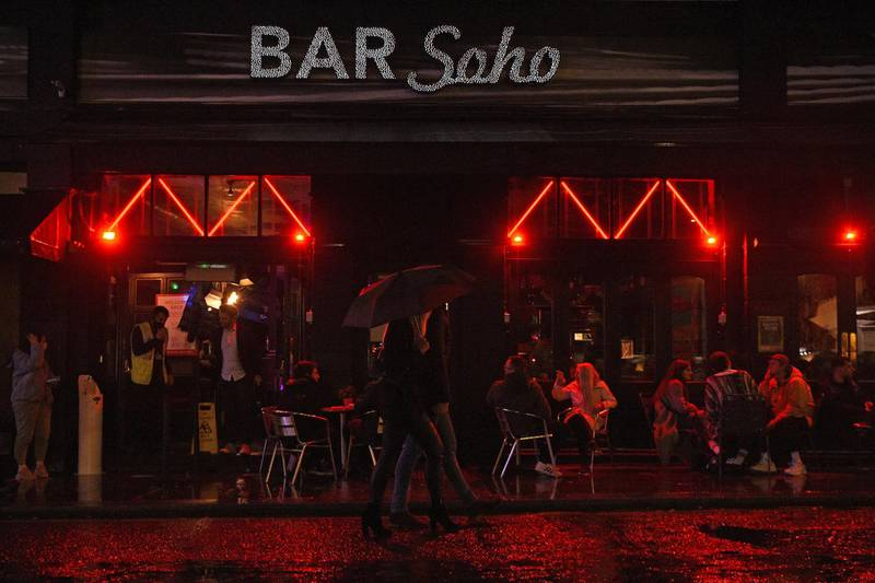 People drink outside a bar in Soho, London, ahead of the 10pm curfew pubs and restaurants are subject to in order to combat the rise in coronavirus cases in England, Friday, Oct. 2, 2020. (Kirsty O'Connor/PA via AP)