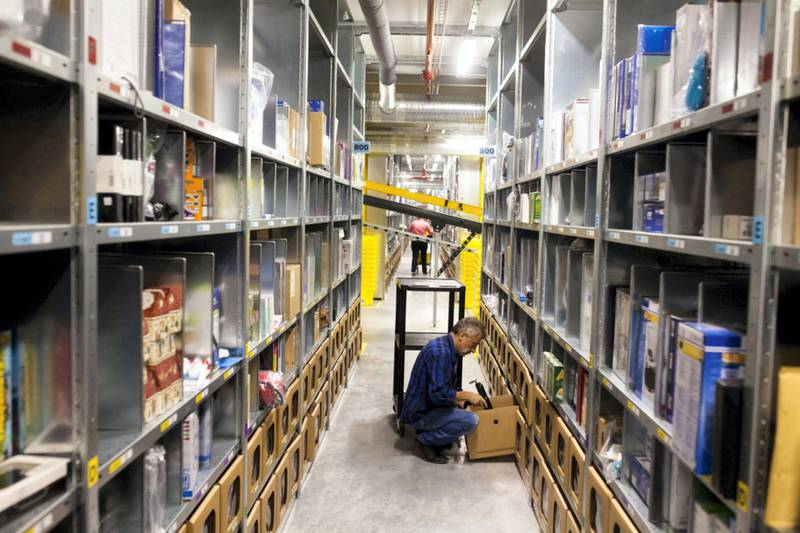 An employee collects a customer's purchase order from storage bays ahead of packaging at the new Amazon Inc. fulfilment center on its official day of opening in Bielany Wroclawskie, Poland, on Tuesday, Oct. 28, 2014. The company announced on Monday that it's taking preorders for a streaming media stick that plugs into a TV, making it possible to watch a range of Internet video services. Photographer: Bartek Sadowski/Bloomberg