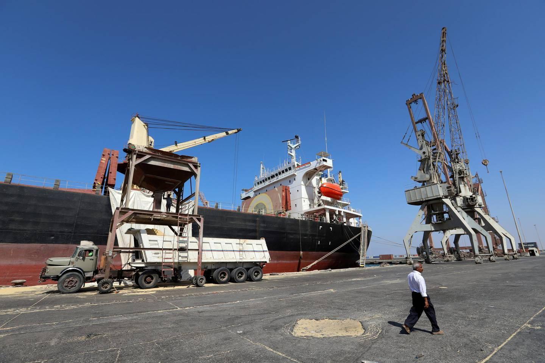 FILE PHOTO: A worker walks past a ship unloading grain at the Red Sea port of Hodeidah, Yemen, January 5, 2019. Picture taken January 5, 2019. REUTERS/Abduljabbar Zeyad/File Photo