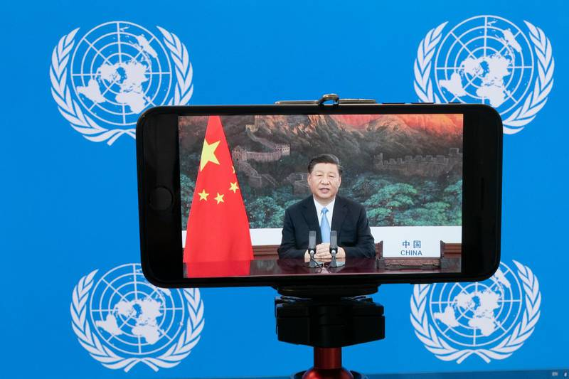 """Chinese President Xi Jinping is seen on a phone screen remotely addressing the 75th session of the United Nations General Assembly, Tuesday, Sept. 22, 2020, at U.N. headquarters. This year's annual gathering of world leaders at U.N. headquarters will be almost entirely """"virtual."""" Leaders have been asked to pre-record their speeches, which will be shown in the General Assembly chamber, where each of the 193 U.N. member nations are allowed to have one diplomat present. (AP Photo/Mary Altaffer)"""