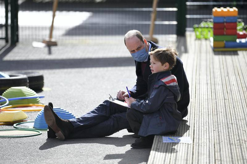 LONDON, ENGLAND - MARCH 11: Prince William, Duke of Cambridge, speaks to a young pupil in the playground during a visit to School 21 in Stratford on March 11, 2021 in London, England. The Duke and Duchess of Cambridge visited the school in east London to congratulate teachers involved in the re-opening of the school following lockdown restrictions. (Photo by Justin Tallis - WPA Pool/Getty Images)