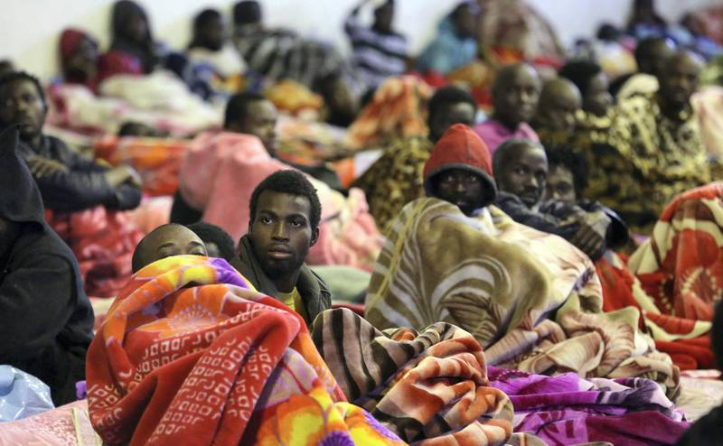 A picture taken on December 11, 2017 shows African migrants sitting and lying in a shelter at the Tariq Al-Matar migrant detention centre on the outskirts of the Libyan capital Tripoli. / AFP PHOTO / Mahmud TURKIA