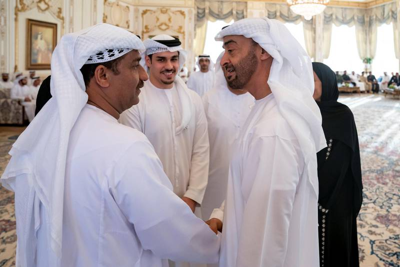 ABU DHABI, UNITED ARAB EMIRATES - July 01, 2019: HH Sheikh Mohamed bin Zayed Al Nahyan, Crown Prince of Abu Dhabi and Deputy Supreme Commander of the UAE Armed Forces (R) receives Ahmed Al Hosani (2nd L), a student who achieved the highest German 'Abitur' examination certificate in high schools across the world. Seen with Khaled Al Hosani (L).  ( Hamad Al Kaabi / Ministry of Presidential Affairs ) ---