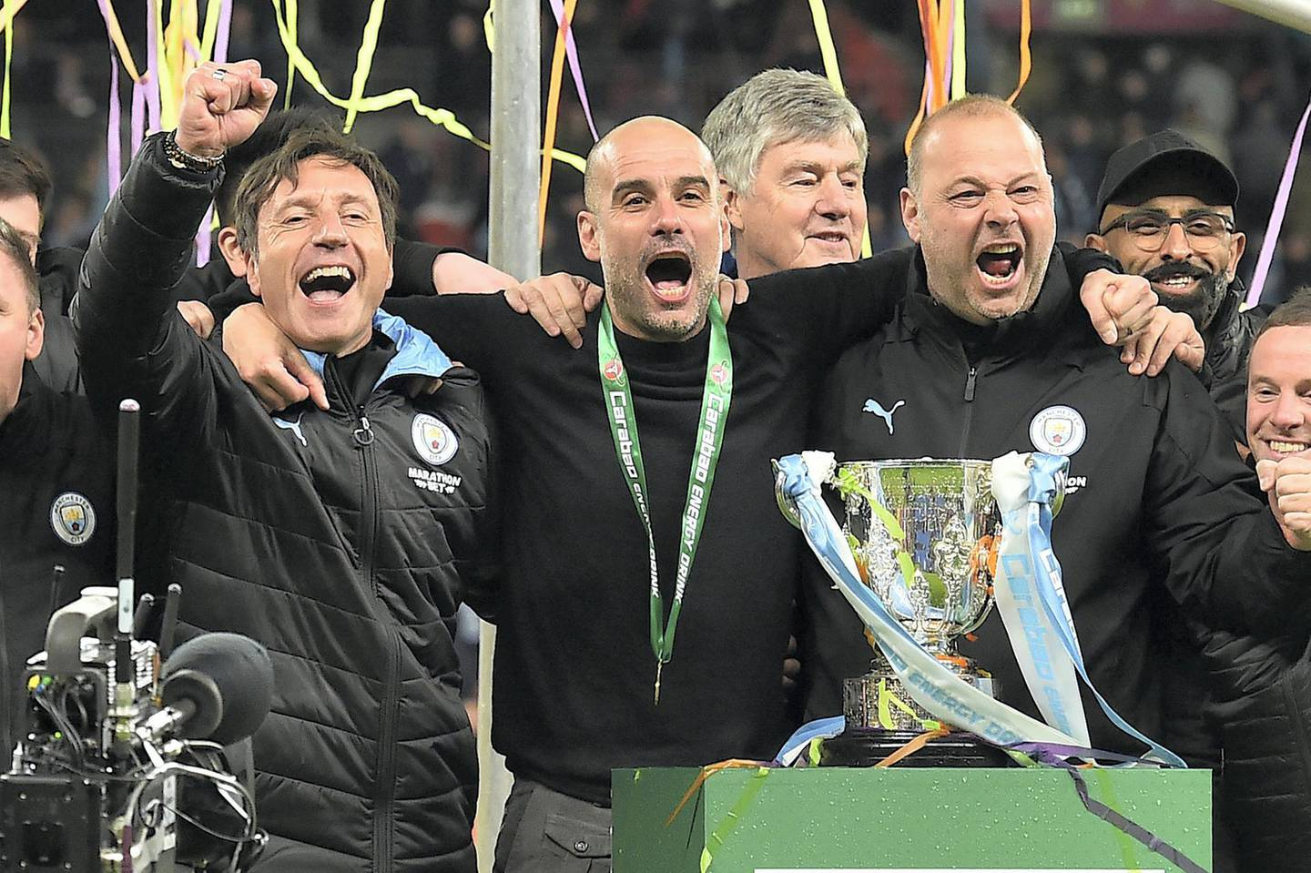 Manchester City's Spanish manager Pep Guardiola (C) celebrates with his backroom staff, Manchester City's Spanish assistant coach Rodolfo Borrell (R) as City players celebrate their win after the English League Cup final football match between Aston Villa and Manchester City at Wembley stadium in London on March 1, 2020. - Manchester City won the game 2-1. (Photo by Glyn KIRK / AFP)