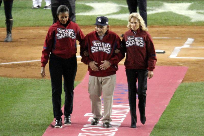 NEW YORK - OCTOBER 28:  New York Yankees legend and Baseball Hall of Famer Yogi Berra (C) is escourted onto the field by First lady Michelle Obama (L) and Dr. Jill Biden, wife of Vice President Joe Biden, prior to Game One of the 2009 MLB World Series between the New York Yankees and the Philadelphia Phillies at Yankee Stadium on October 28, 2009 in the Bronx borough of New York City.  (Photo by Chris McGrath/Getty Images)