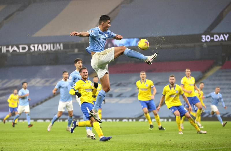 MANCHESTER, ENGLAND - JANUARY 13: Rodrigo of Manchester City stretches as he jumps for the ball during the Premier League match between Manchester City and Brighton & Hove Albion at Etihad Stadium on January 13, 2021 in Manchester, England. Sporting stadiums around England remain under strict restrictions due to the Coronavirus Pandemic as Government social distancing laws prohibit fans inside venues resulting in games being played behind closed doors. (Photo by Clive Brunskill/Getty Images)
