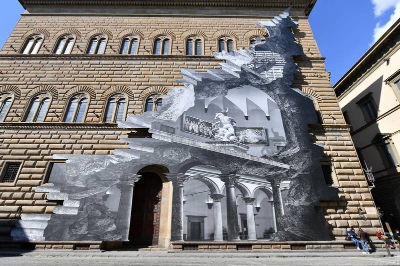 An art installation on the facade of Strozzi Palace by French contemporary artist JR titled 'La Ferita (The Wound)' shows an optical illusion of a black and white interior of the elegant Renaissance palace, as the artist's efforts to make a statement on accessibility to culture in the coronavirus disease (COVID-19) era, in Florence, Italy, March 19, 2021. REUTERS/Jennifer Lorenzini