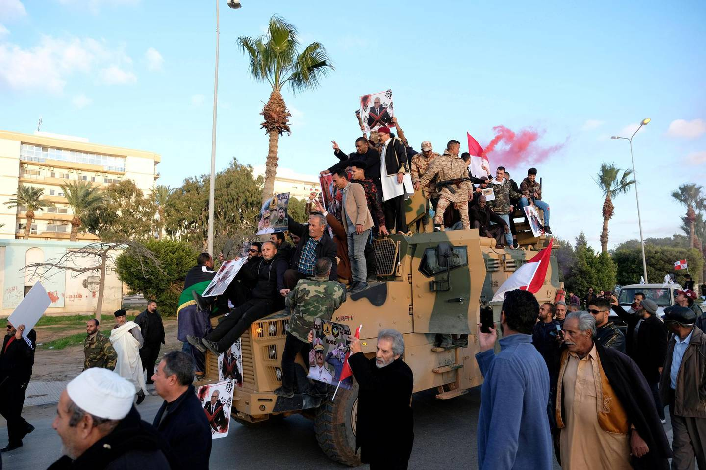 FILE PHOTO: Supporters of Libyan National Army (LNA) commanded by Khalifa Haftar, celebrate on top of a Turkish military armored vehicle, which LNA said they confiscated during Tripoli clashes, in Benghazi, Libya January 28, 2020. REUTERS/STAFF/File Photo