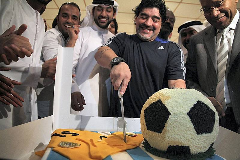 """EDITOR'S NOTE--RESTRICTED TO EDITORIAL USE - MANDATORY CREDIT """"AFP PHOTO /AL-WASL CLUB""""  - NO MARKETING NO ADVERTISING CAMPAIGNS - DISTRIBUTED AS A SERVICE TO CLIENTS -  A handout picture made available by the UAE's Al-Wasl club shows Argentinian football legend and Al-Wasl team coach, Diego Maradona, cutting a cake during a celebration marking his 51st birthday in Dubai, on October 30, 2011. Maradona was presented with a special jersey signed by all the players on the team.  AFP PHOTO/HO/AL-WASL CLUB (Photo by - / AL-WASL CLUB / AFP)"""
