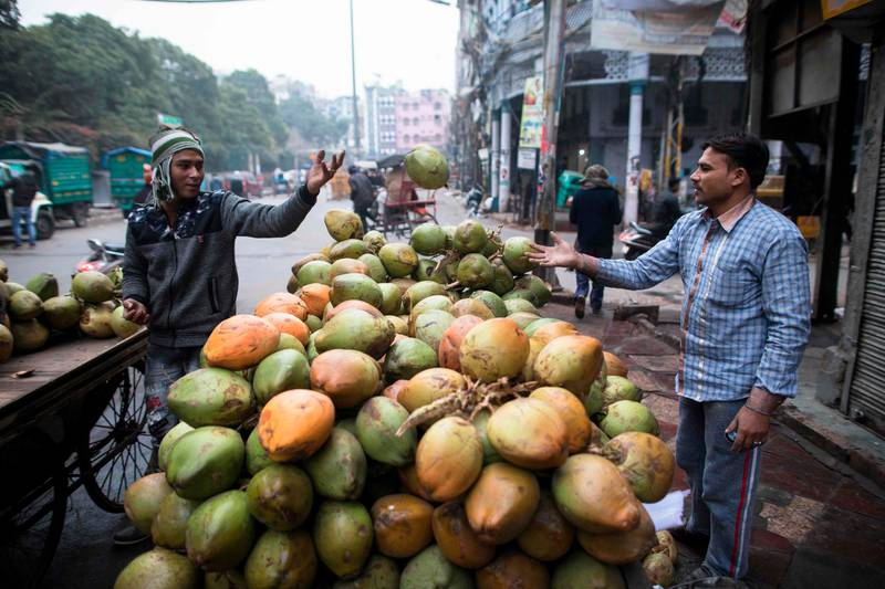 A worker passes a coconut to another man as they prepare a street stall in the old quarters of New Delhi on December 27, 2019. / AFP / XAVIER GALIANA