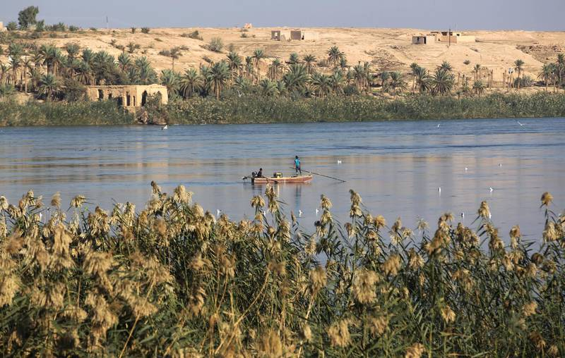 A picture taken on November 13, 2018 shows a fishing boat crossing in the Euphrates River in al-Qaem city in the western Iraqi province of Anbar on the border with Syria, opposite the Albu Kamal in the Syrian province of Deir Ezzor. (Photo by AHMAD AL-RUBAYE / AFP)