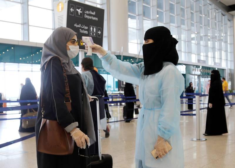 A security woman checks the temperature of a woman at Riyadh International Airport, after Saudi Arabia reopened domestic flights, following the outbreak of the coronavirus disease (COVID-19), in Riyadh, Saudi Arabia May 31, 2020. REUTERS/Ahmed Yosri