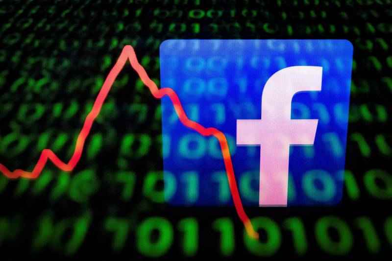 """(FILES) This file illustration picture taken on April 26, 2018 in Paris shows the logo of social network Facebook displayed on a screen and reflected on a tablet.  Facebook on May 23, 2019, said it recently disabled billions of bogus accounts set up by """"bad actors"""" and that five percent of active accounts are likely fakes. Facebook disabled 2.19 billion accounts in the first quarter of this year, nearly double the number of accounts nixed in the prior three-month period, according to vice president of integrity Guy Rosen. / AFP / Lionel BONAVENTURE"""