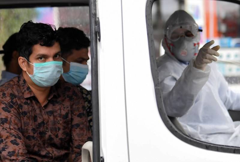 Foreign workers who have tested positive to the novel coronavirus at a testing centre in the Naif area of the Gulf Emirate of Dubai, wait in a bus before being transported to  a specialised centre for isolation and treatment, on April 15, 2020.  / AFP / KARIM SAHIB