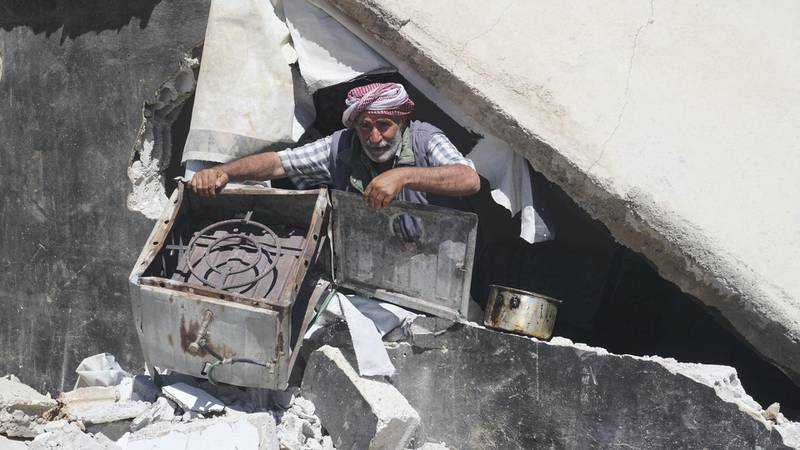 Nasser al-Kanj pulls out a broken stove from the rubble of his home destroyed by the Lebanese army in Al Shouhada camp, Arsal. Sunniva Rose / The National