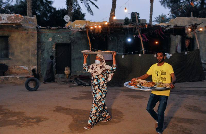 People, who try to improve their living conditions by selling food to tourists, carry trays with meals in their village at Saqqara in Giza, Egypt, April 27, 2021. Picture taken April 27, 2021. REUTERS/Shokry Hussien